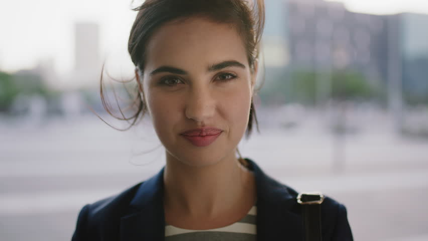 Portrait of successful young business woman smiling at camera running hand through hair enjoying urban lifestyle windy city commuting | Shutterstock HD Video #1010500418