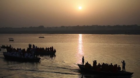 Varanasi / India 27 March 2018 Early morning People rowing the row boat on golden surface water of river ganga at sunrise in Varanasi Ghat Uttar Pradesh India