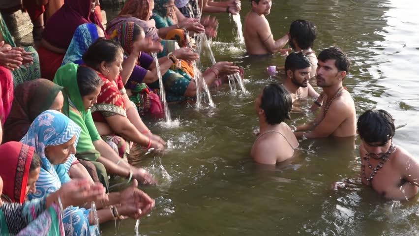Varanasi / India 27 March 2018 Unidentified women and men taking ritual bath in the river Ganga at Varanasi  Uttar Pradesh India