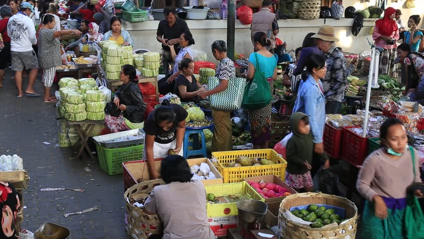 UBUD, BALI, INDONESIA - APRIL 09, 2018 : Poor Indonesian people selling and buying healthy food at the morning market in village Ubud, island Bali, Indonesia. Early morning fruit and vegetable market