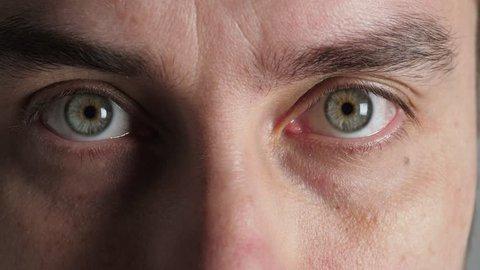 Man blinking his eyes. Closeup on young man face