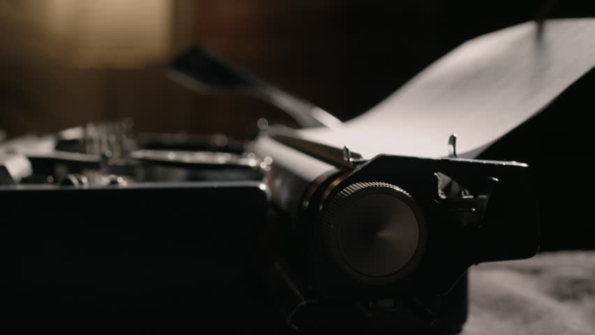 Carriage return knob pushing in and out of focus while typing on a vintage typewriter