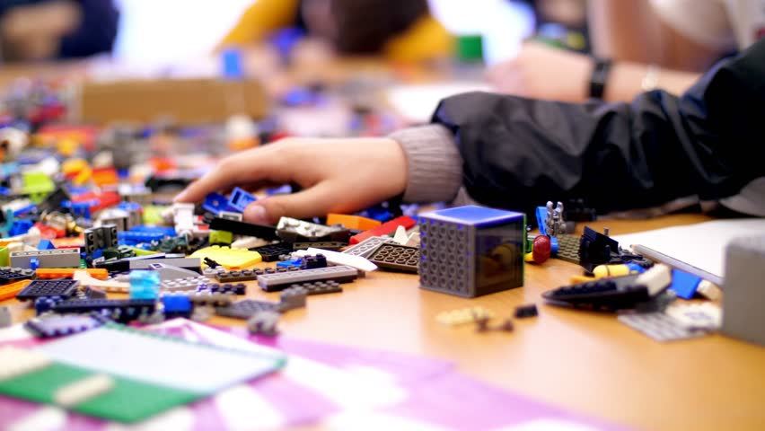 On the table there are scattered a lot of details from the children's designer, cubes, wires, boards, wheels, multicolored small robots, machines. children are fond of robotics, programming, modeling, | Shutterstock HD Video #1010537228