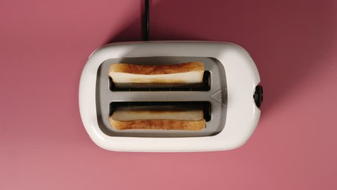 TOP VIEW: Roasted bread jump out from a white toaster on a pink table