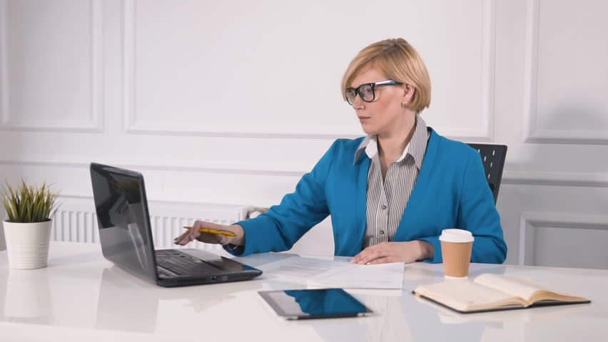 Focused woman dealing with documents at white square desk, wearing marine blue jacket and striped shirt, using black laptop to do the task, indoor shot in big white office