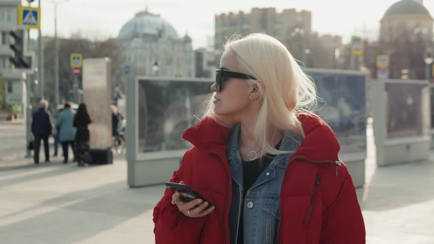 Young happy teenage girl using phone and having fun in spring park. Blonde happy model woman portrait student in down jacket and sunglasses on street smartphone. | Shutterstock HD Video #1010564768