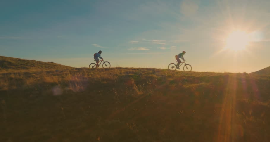 Aerial tracking of mountain bikers on cross-country cycling in amazing sunlight. #1010578208