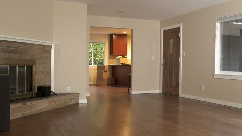 Couple walking through front door of new home, woman blindfolded and surprised, full length.