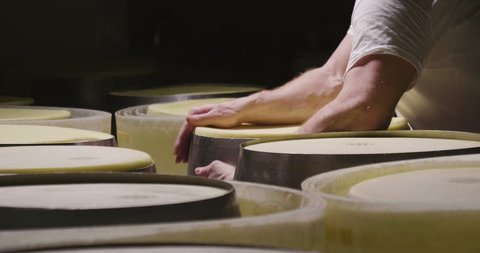 A cheesemaker controls the seasoning of Parmesan cheese, which has to mature for many months. The processing is done following the ancient Italian tradition.