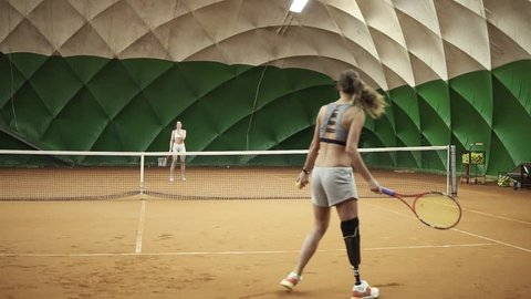 Backside footage of two athletic girls playing tennis in a covered tennis court. Woman in the frame with a leg prosthesis
