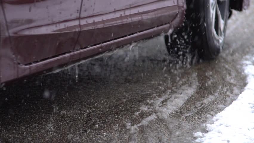 Car tires driving through a slushy storm, in slow motion