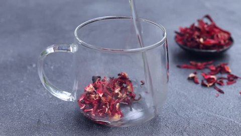 Making hibiscus tea with boiling water in a glass cup. Slate background.