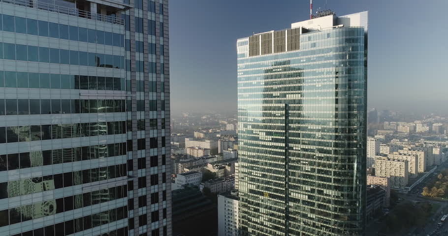 Drone footage in between skyscrapers and glass office buildings in Warsaw city center. Shot is taken during a misty but sunny day in Polish capital city.   | Shutterstock HD Video #1010660138