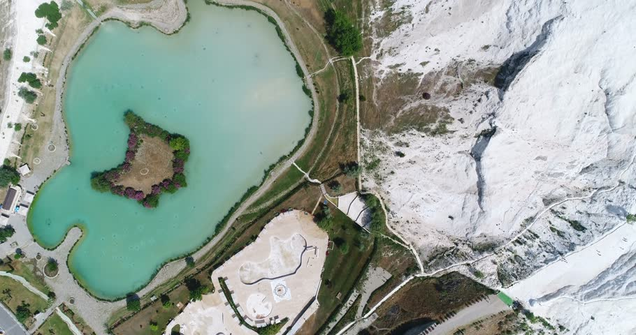 Aerial. Camera moves forward. Top down view. Pamukkale - famous  gleaming white calcite travertines (terraces) on the cliff. Turkey, 4K.