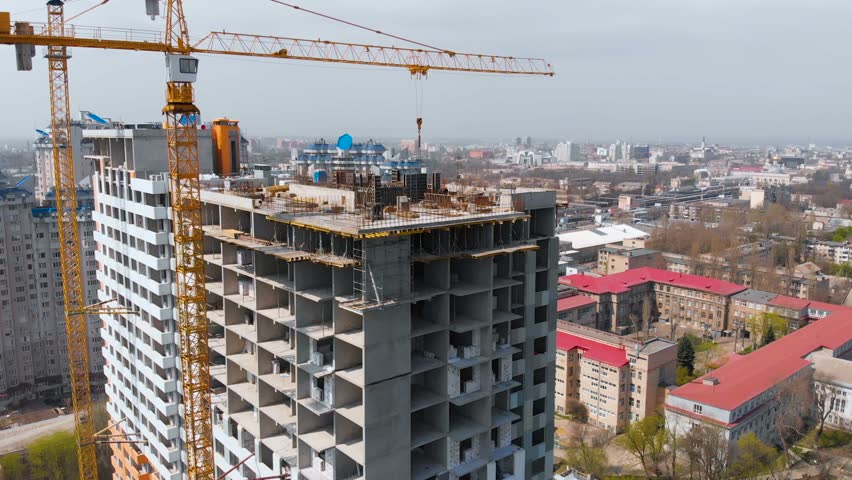 Construction site with a bird's eye in a megacity. Video shooting with drone. New house in a new residential complex. Flying over the construction site. New house next door in the city. 4K.