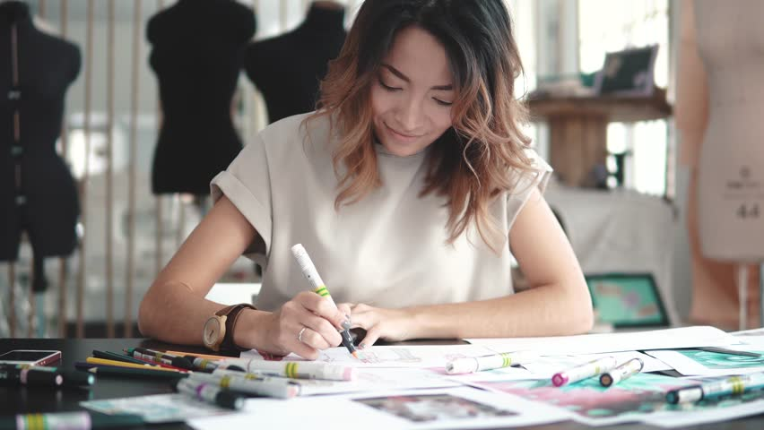 A young Asian woman working in a clothing store. A fashion designer makes outlines on paper. | Shutterstock HD Video #1010675018