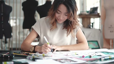 A young Asian woman working in a clothing store. A fashion designer makes outlines on paper.