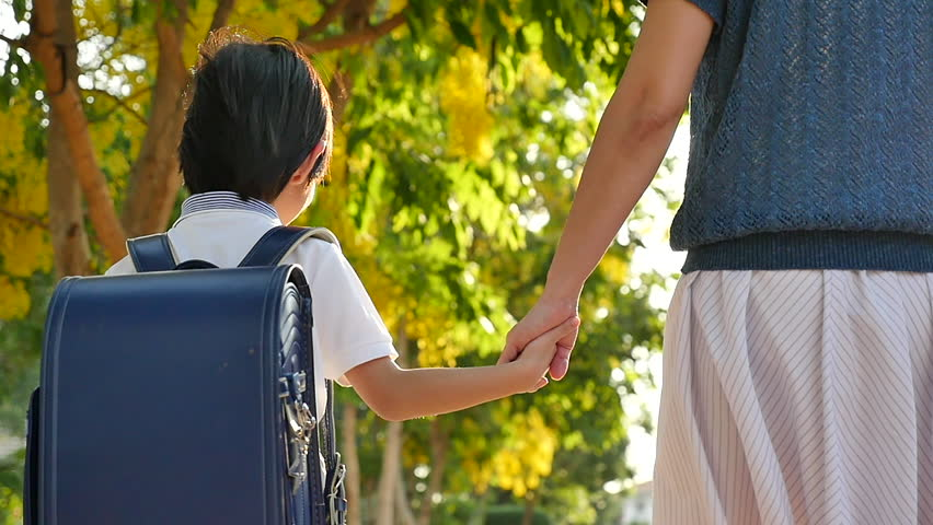 Asian mother holding hand of little son with backpack outdoors, back to school slow motion | Shutterstock HD Video #1010717768