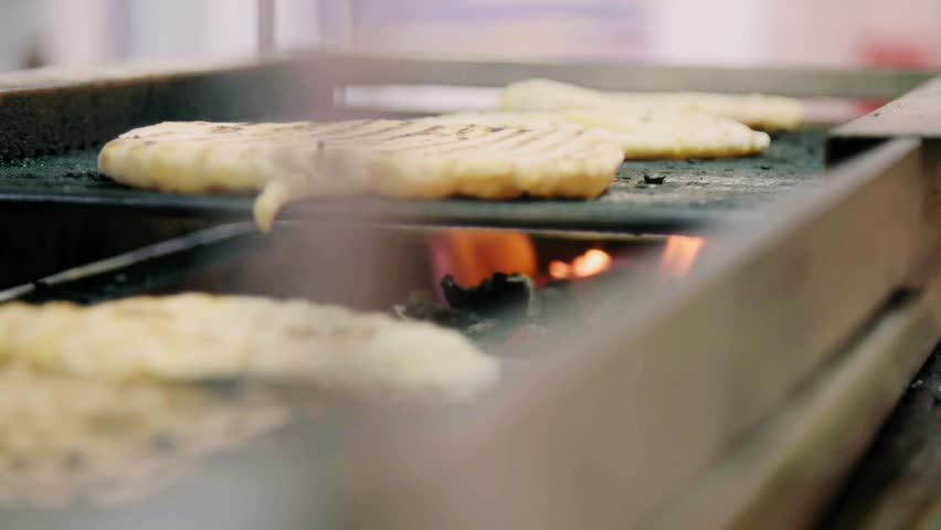 Detail shot of a cook's hands baking flatbreads on the grill