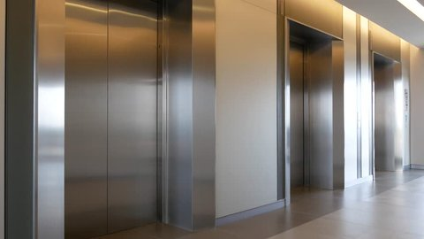 Modern steel elevator open and close door cabins in a business lobby or Hotel, Store, interior, office,perspective wide angle. Three elevators in hotel lobby.