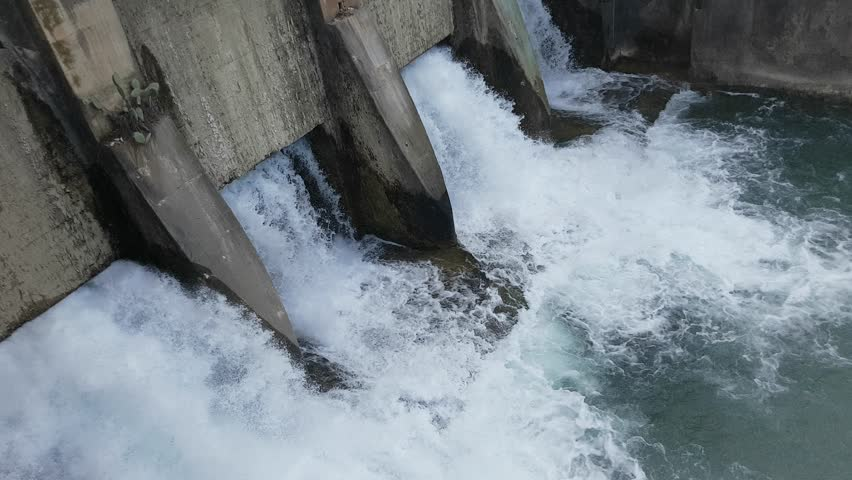 Spring flood water flowing on hydroelectric power station dam | Shutterstock HD Video #1010763638