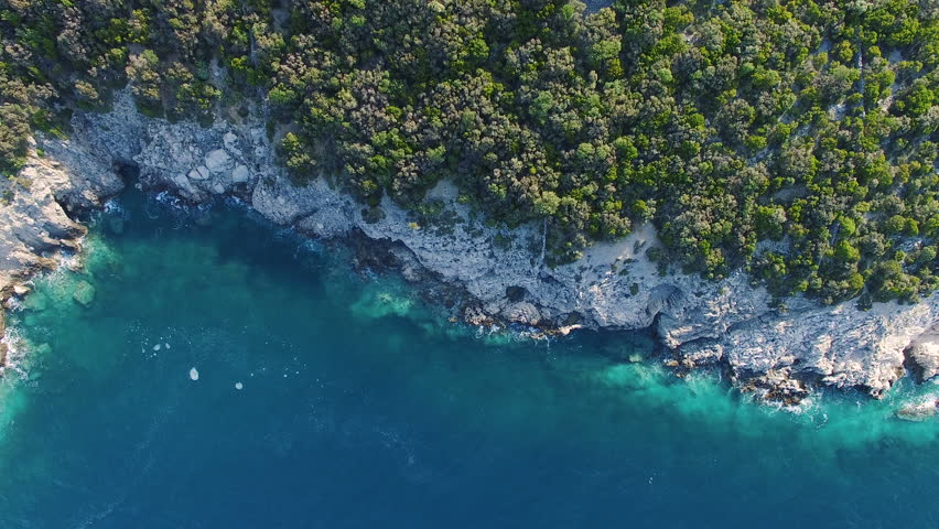 CRES, CROATIA: Aerial view of cliffs tracking slowly to sea at Lubenice beach. 4k drone video downward and backward.