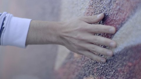 Man Walks Along Colorful Mural Wall And Touches The Side Of It (Slow Motion, Closeup Of His Hand)