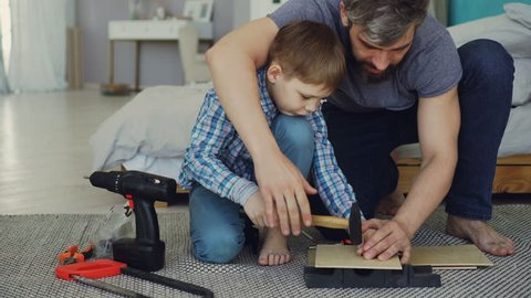 Father bearded man is teaching his son how to use hammer driving nail in piece of wood together sitting on floor at home. Instruments, tools and furniture are visible.