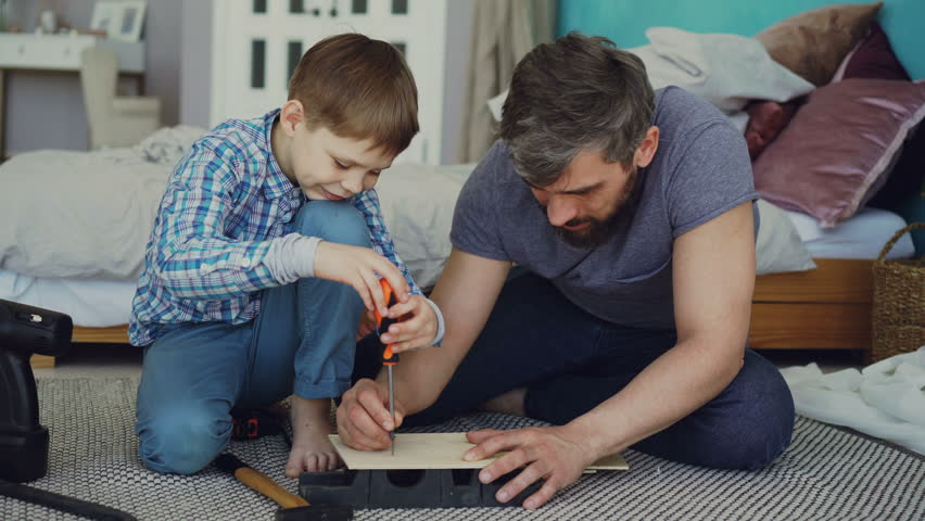 Curious child is driving screw in piece of wood with screwdriver and his dad is holding wooden sheet and teaching him basics of woodwork. United family concept. | Shutterstock HD Video #1010801258