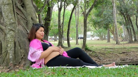 Asian pregnant girl relax and sits under a tree in a pubic park.