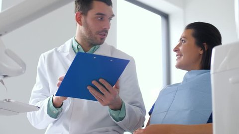 medicine, dentistry and healthcare concept - male dentist with clipboard talking to female patient at dental clinic office