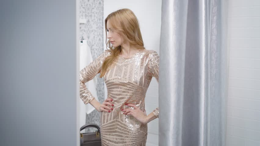 Side view shot of a charming woman posing in a new dress in changing room in a boutique. | Shutterstock HD Video #1010846108