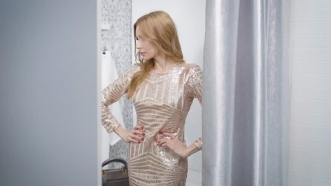 Side view shot of a charming woman posing in a new dress in changing room in a boutique.