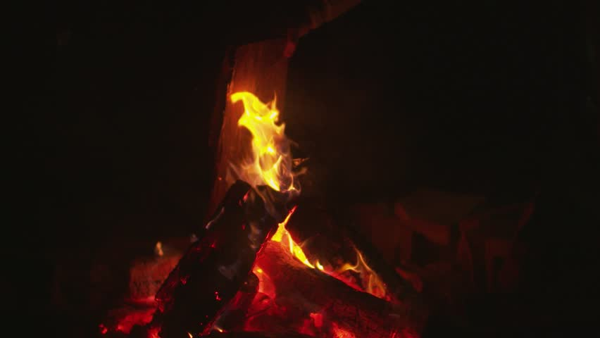 A campfire in slow motion as logs/stick are being place onto it.