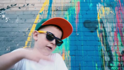 Portrait of a 5-year-old street dancer, A cool 5 year old child dances in sunglasses near a brick wall with graffiti