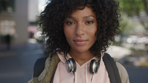 portrait of young attractive african american woman staring pensive in city street wearing headphones casual lifestyle