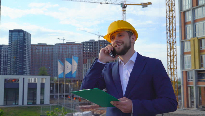 A young male orchid examines a project under construction against the background of buildings. Close-up portrait of a man. the man is holding a green paper tablet. the person is talking on the phone | Shutterstock HD Video #1010921678