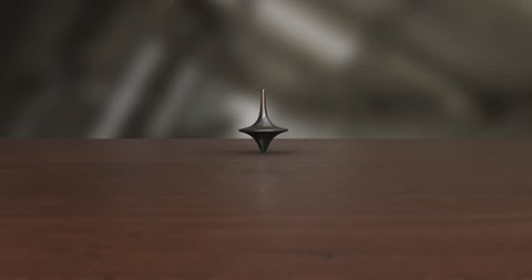 Smoothly Spinning Metal Top Looping Endlessly on Wood from the Front