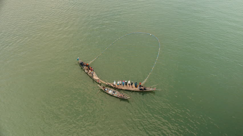 Upper view on fishers in small boats lifting together a large net out of water