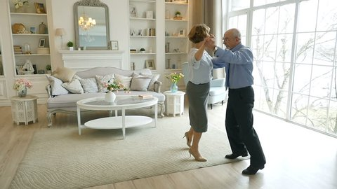 Slow motion, old retired people and leisure activities, happy senior couple dancing valse for fun at living room, elderly couple at home