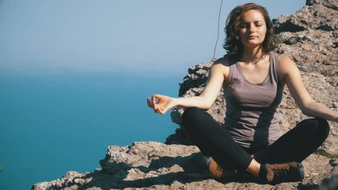 Woman traveler meditates in mountains, sitting on top of a cliff in the lotus position. Beautiful young woman practicing yoga and positions outdoors on an incredible cliff top setting. Yalta, Crimea