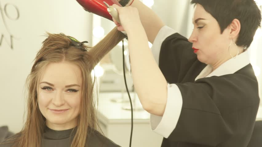 Hairdresser making woman hairstyling long hair with dryer and brush in beauty salon. Close up haircutter drying woman hair with dryer and hairbrush after washing and cutting in hairdressing salon
