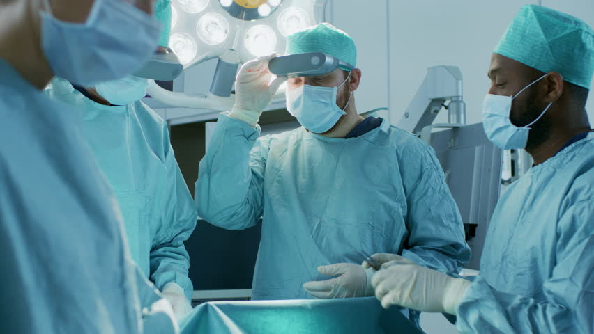 Surgeons Wearing Augmented Reality Glasses Perform State of the Art Mixed Reality Surgery in High Tech Hospital. Doctors and Assistants Working in Operating Room. Shot on RED EPIC-W 8K Helium Camera.