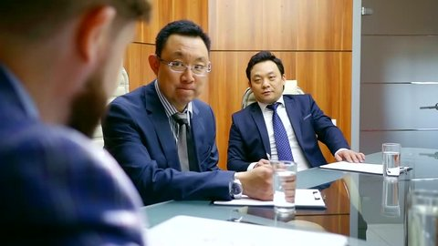 Asian business partners look attentively at a European who talks about a trading company