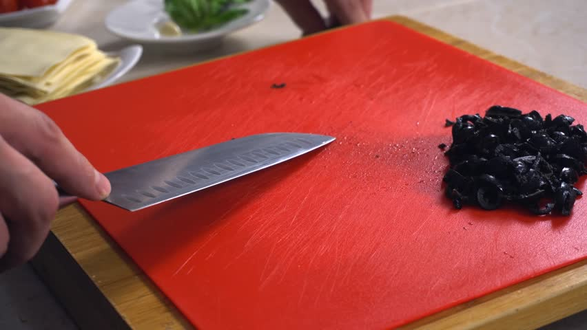 A professional chef cutting capers on a red cooking board very quickly. The preparation of food for cooking vegetarian dishes. The salted and pickled caper bud is often used as a seasoning or garnish.