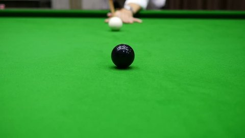 Slow motion of man playing snooker hit black ball into the middle pocket with screw back