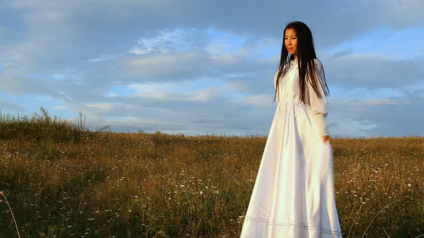 young Asian woman standing in the field, laughing and waving a white dress. in the sunset light on the background of the field with white flowers, the camera plan in full growth. spring-autumn