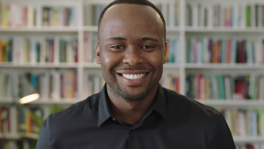 Young african american man portrait smiling looking at camera standing in library entrepreneur is new business owner standing confidently feeling good emotions | Shutterstock HD Video #1011075758