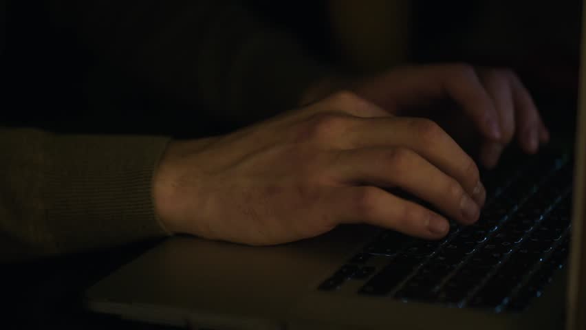 Close up of male hands typing text or programming code in computer in natural ambient light at late evening. Stock