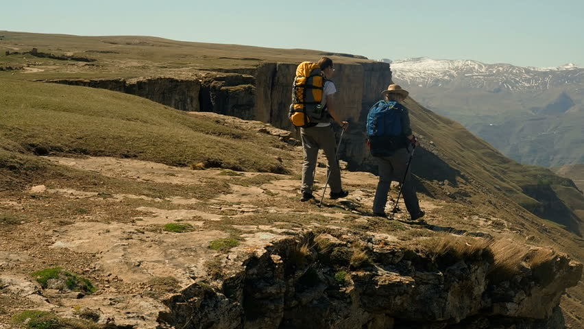 Hikers with backpacks walking  enjoying the view of valley. Two hikers on the trail in the Caucasian mountains. Young active people travelling with backpacks during summer holiday.    Shutterstock HD Video #1011095858